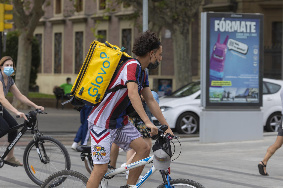 Zaragoza, Spain - August 18, 2020: Glovo rider working with face mask, due to the coronavirus pandemic, in the central area of Zaragoza.