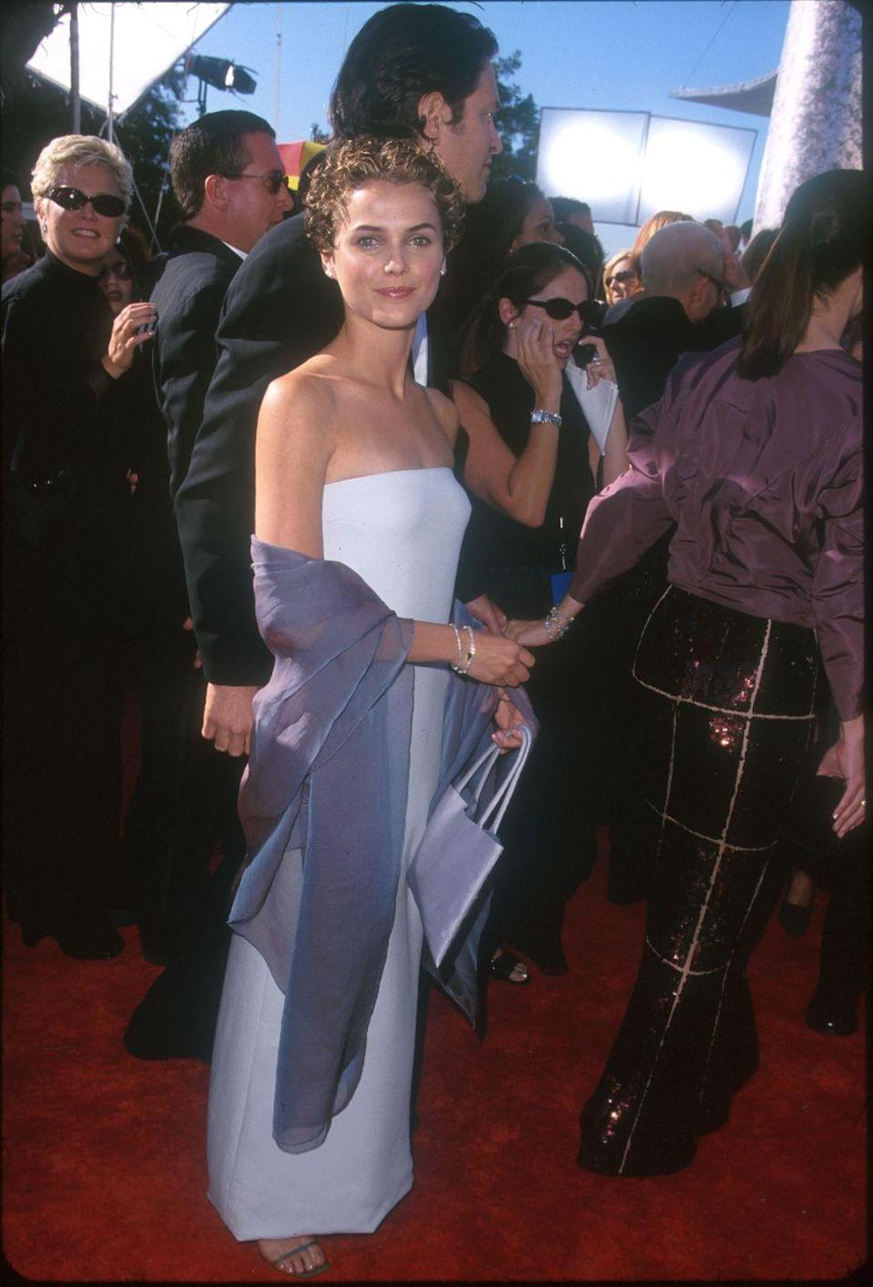 <p>Russell wore a simple gown and her infamous pixie to the Emmy Awards in 1999. </p>