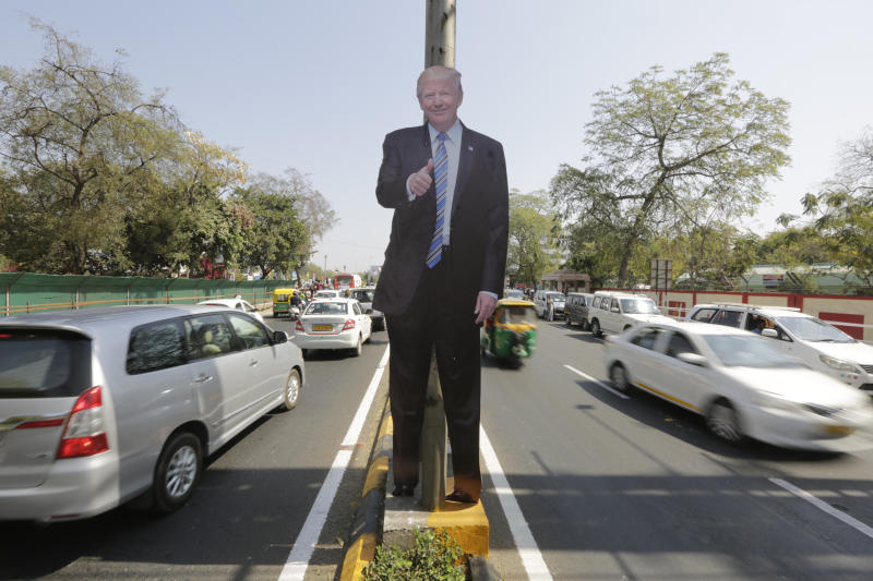 A life size cut-out of U.S. president Donald Trump stands on a road divider, ahead of his visit in Ahmedabad, India, Saturday, Feb. 22, 2020. To welcome Trump, who last year likened Modi to Elvis Presley for his crowd-pulling power at a joint rally the two leaders held in Houston, the Gujarat government has spent almost $14 million on ads blanketing the city that show them holding up their hands, flanked by the Indian and U.S. flags. (AP Photo/Ajit Solanki)