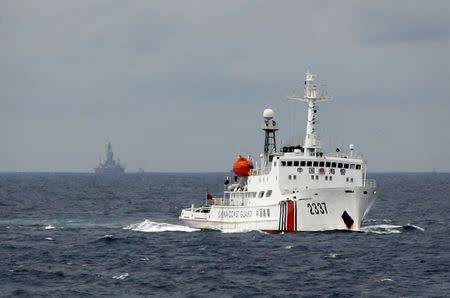 Chinese Coast Guard vessel passes near the Chinese oil rig Haiyang Shi You 981 in the South China Sea