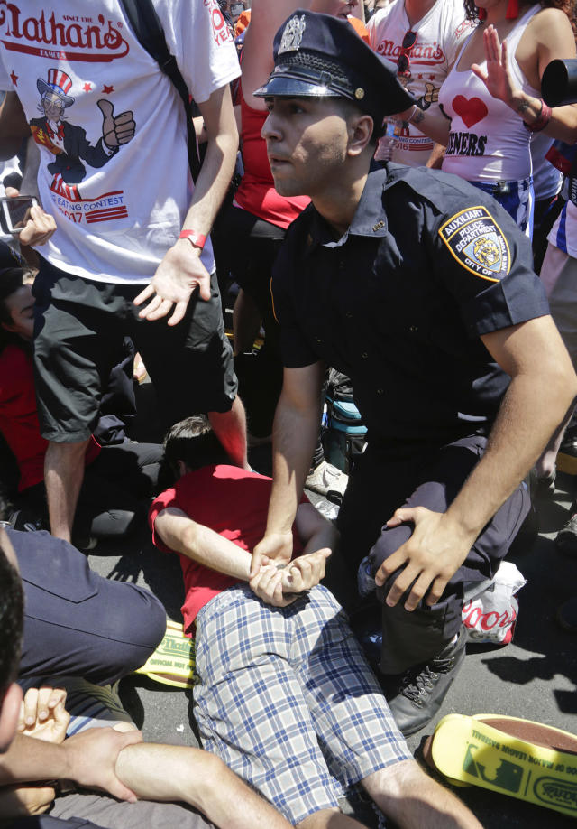 <p>Police arrest an animal rights activist as they try to protest at the Nathan's Annual Famous International Hot Dog Eating Contest won by Joey Chestnut, Tuesday July 4, 2017, in New York. (AP Photo/Bebeto Matthews) </p>