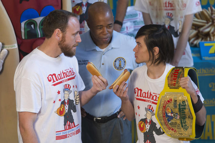 <p>Matt Stonie, right, reigning hot dog-eating champion, stares down eight-time champion Joey Chestnut during the official weigh in for Nathans Famous hot dog eating contest, July 1, 2016, in New York. Brooklyn borough President Eric Adams stand between the men. (Photo: Mary Altaffer/AP) </p>