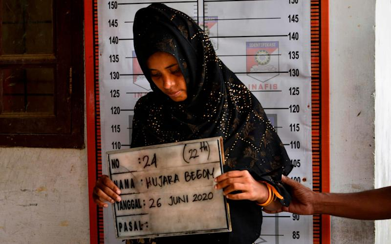 A Rohingya woman from Myanmar goes through an identification procedure by Indonesia police - CHAIDEER MAHYUDDIN/AFP
