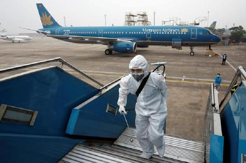A health worker sprays disinfectant outside a Vietnam Airlines airplane to protect from the recent coronavirus outbreak, at Noi Bai airport in Hanoi, Vietnam. (REUTERS)
