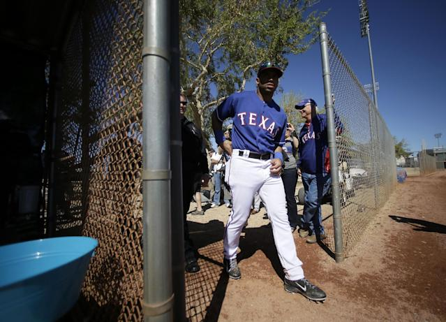 Seattle Seahawks quarterback Russell Wilson walks on to the practice field after signing autographs during spring training baseball practice with the Texas Rangers, Monday, March 3, 2014, in Surprise, Ariz. (AP Photo/Tony Gutierrez)
