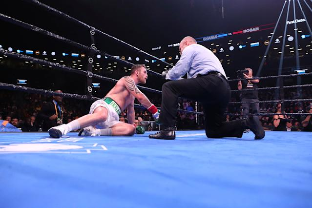 Ireland's Dennis Hogan receives a count during the seventh round of his WBC middleweight boxing match against Jermall Charlo on Saturday, Dec. 7, 2019, in New York. (AP Photo/Michael Owens)