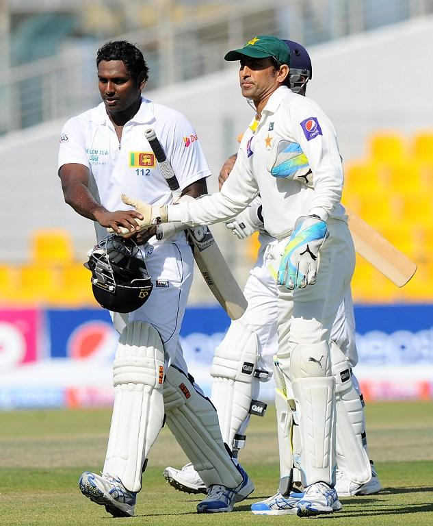 Sri Lankan cricket captain Angelo Mathews (L) is congratulated by Pakistan wicketkeeper Younis Khan (R) he leaves the pitch at the end of the Sri Lankan second innings during the final day of the first cricket Test match between Pakistan and Sri Lanka at the Sheikh Zayed Stadium in Abu Dhabi on January 4, 2014. AFP PHOTO/Ishara S. KODIKARA