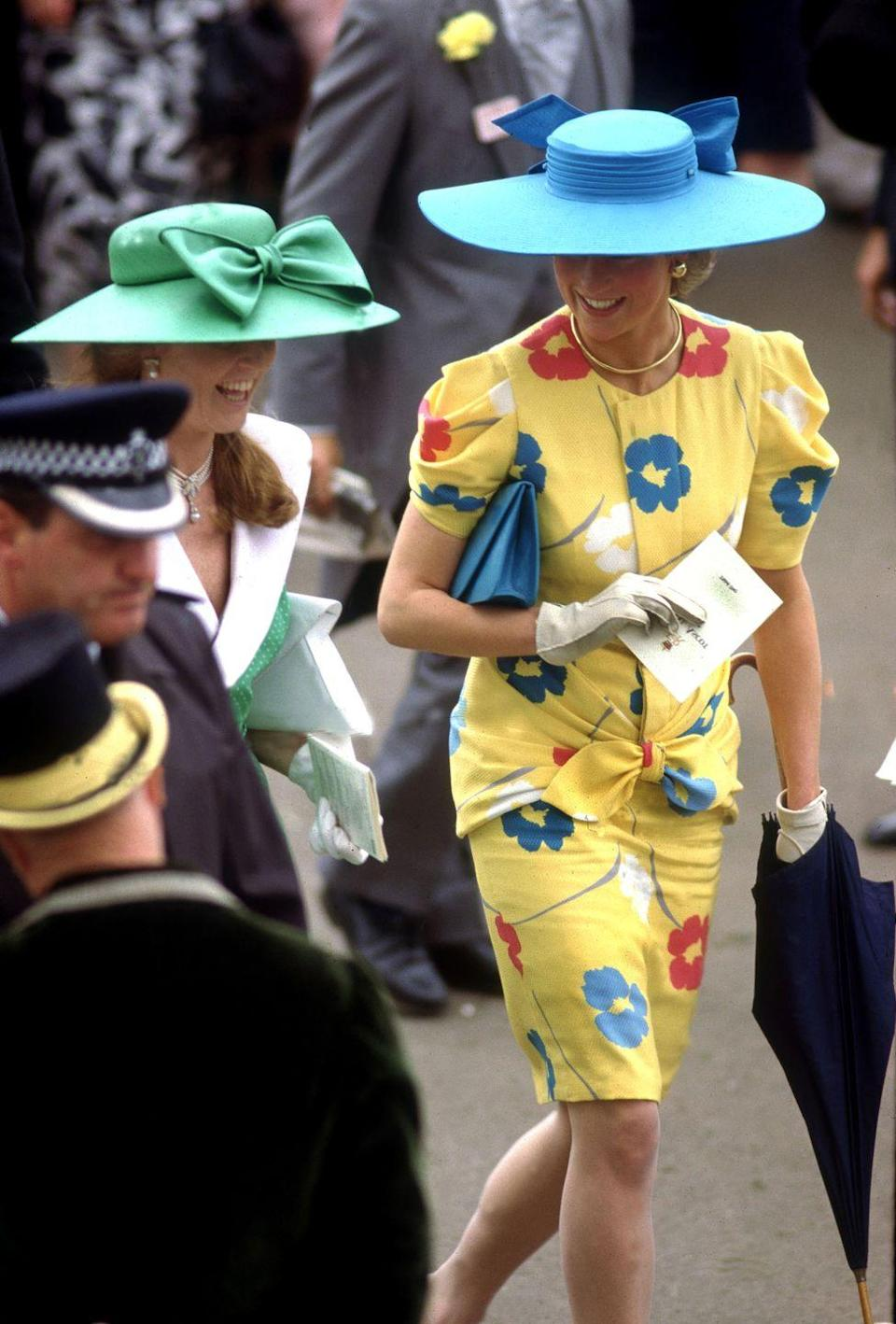 <p>In a yellow floral dress and blue hat and clutch in the Royal Enclosure at the Royal Ascot. </p>