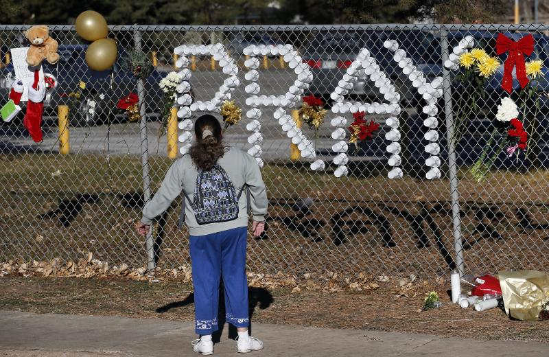 A woman pauses before a makeshift memorial three days after a shooting attack at Arapahoe High School in Centennial, Colo., Monday, Dec. 16, 2013. During the attack, the shooter shot a classmate in the head at close range with a shotgun, before killing himself. (AP Photo/Brennan Linsley)