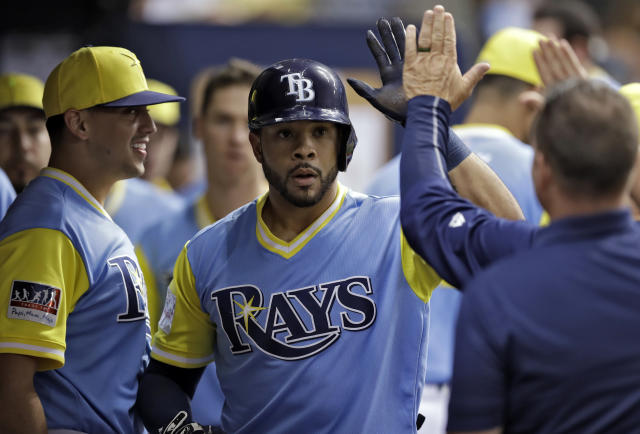 Tampa Bay Rays' Tommy Pham, center, celebrates with teammates in the dugout after his home run off Boston Red Sox relief pitcher Brandon Workman during the seventh inning of a baseball game Saturday, Aug. 25, 2018, in St. Petersburg, Fla. (AP Photo/Chris O'Meara)