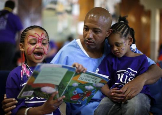 "Donte (R), 34, who said he has one year left in prison, reads a book with his daughters Cieara (L), 7, and Nicole, 3, at San Quentin state prison for a Father's Day visit organized by ""Get on the Bus"" in San Quentin California, June 8, 2012."