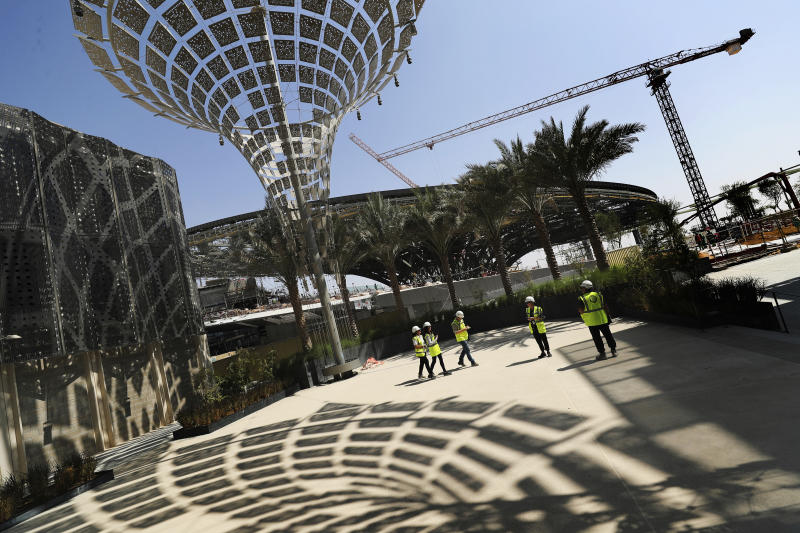 "In this Oct. 8, 2019, photo, Associated Press journalists visit the Sustainability Pavilion at the under construction site of the Expo 2020 in Dubai, United Arab Emirates. Its Sustainability Pavilion, which recalls the towers of New York's 1964 world's fair, will be covered in solar panels and surrounded by similarly paneled ""energy trees"" to make it a zero-energy structure. (AP Photo/Kamran Jebreili)"