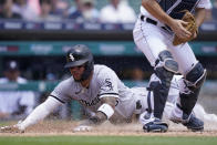Chicago White Sox's Yoan Moncada scores ahead of the throw to Detroit Tigers catcher Jake Rogers during the fourth inning of a baseball game, Sunday, June 13, 2021, in Detroit. (AP Photo/Carlos Osorio)