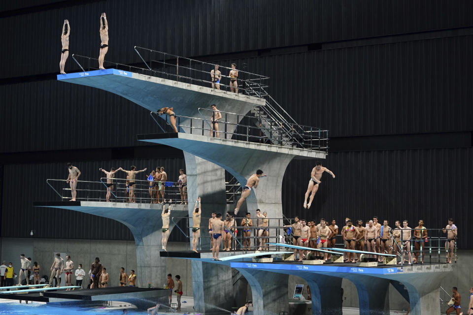 FILE - In this May 1, 2021, file photo, athletes warm up prior to the men's synchronized 10-meter platform preliminary at the FINA Diving World Cup, served as a qualifying competition for Diving at the Tokyo 2020 Olympic Games, at the Tokyo Aquatics Centre in Tokyo. Public sentiment in Japan has been generally opposed to holding the Tokyo Olympics and Paralympics. This is partly based of fears the coronavirus will spike as almost 100,000 people — athletes and others — enter for both events.(AP Photo/Eugene Hoshiko, File)