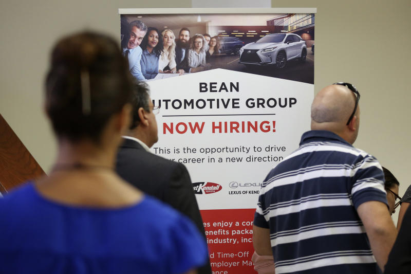 FILE - In this Sept. 18, 2019, file photo people stand in line to inquire about jobs available at the Bean Automotive Group during a job fair designed for people fifty years or older in Miami. On Wednesday, Dec. 4, payroll processor ADP reports on how many jobs its survey estimates U.S. companies added in November. (AP Photo/Lynne Sladky, File)