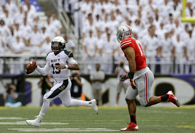 Navy quarterback Keenan Reynolds, left, looks for a receiver as he tries to evade Ohio State defensive lineman Rashad Frazier during the first half of an NCAA college football game in Baltimore, Saturday, Aug. 30, 2014. (AP Photo/Patrick Semansky)