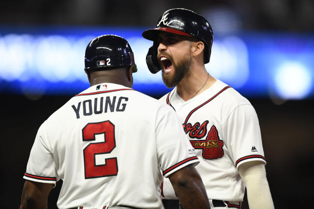 Atlanta Braves' Ender Inciarte shouts as coach Eric Young talks to him after Inciarte hit an RBI single during the seventh inning of the team's baseball game against the New York Mets, Wednesday, Aug.14, 2019, in Atlanta. (AP Photo/John Amis)