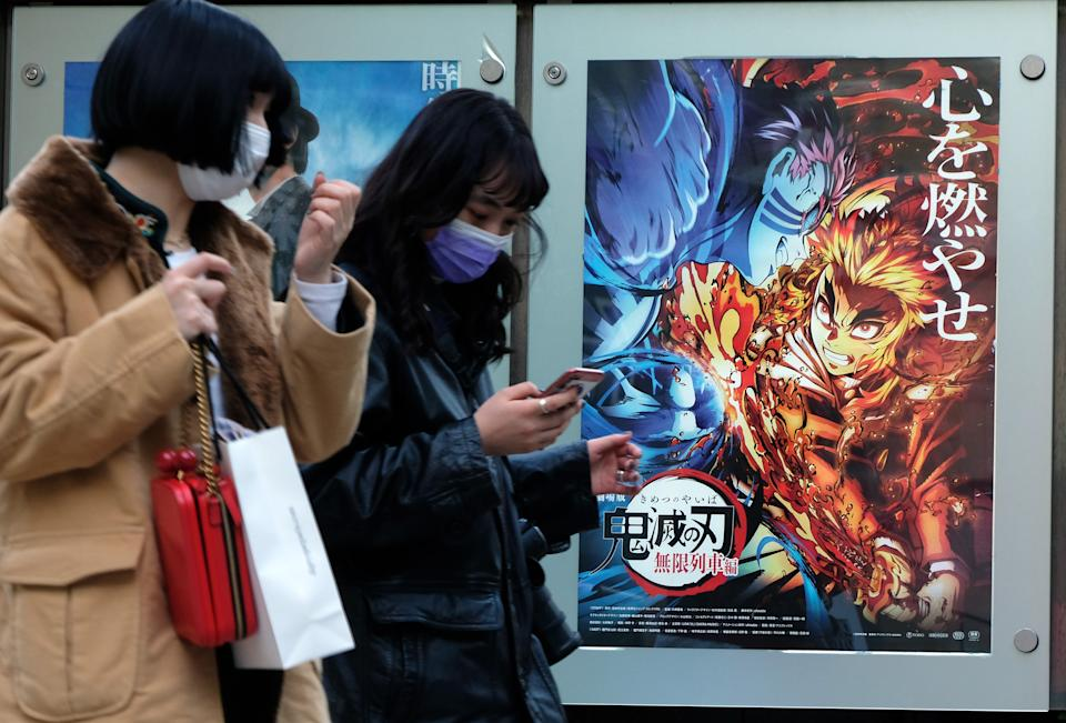 In this picture taken on December 16, 2020, pedestrians walk past a poster promoting the anime movie Demon Slayer -- Kimetsu no Yaiba the Movie: Mugen Train -- at a cinema in Tokyo. - An anime epic in which a teenager hunts down and beheads demons has become the surprise sensation of Japanese cinema during the pandemic, and could soon be the country's top-grossing film of all time. (Photo by Kazuhiro NOGI / AFP) / To go with AFP story  Japan-entertainment-film-anime-health-virus, FOCUS by Mathias CENA, Katie Forster (Photo by KAZUHIRO NOGI/AFP via Getty Images)