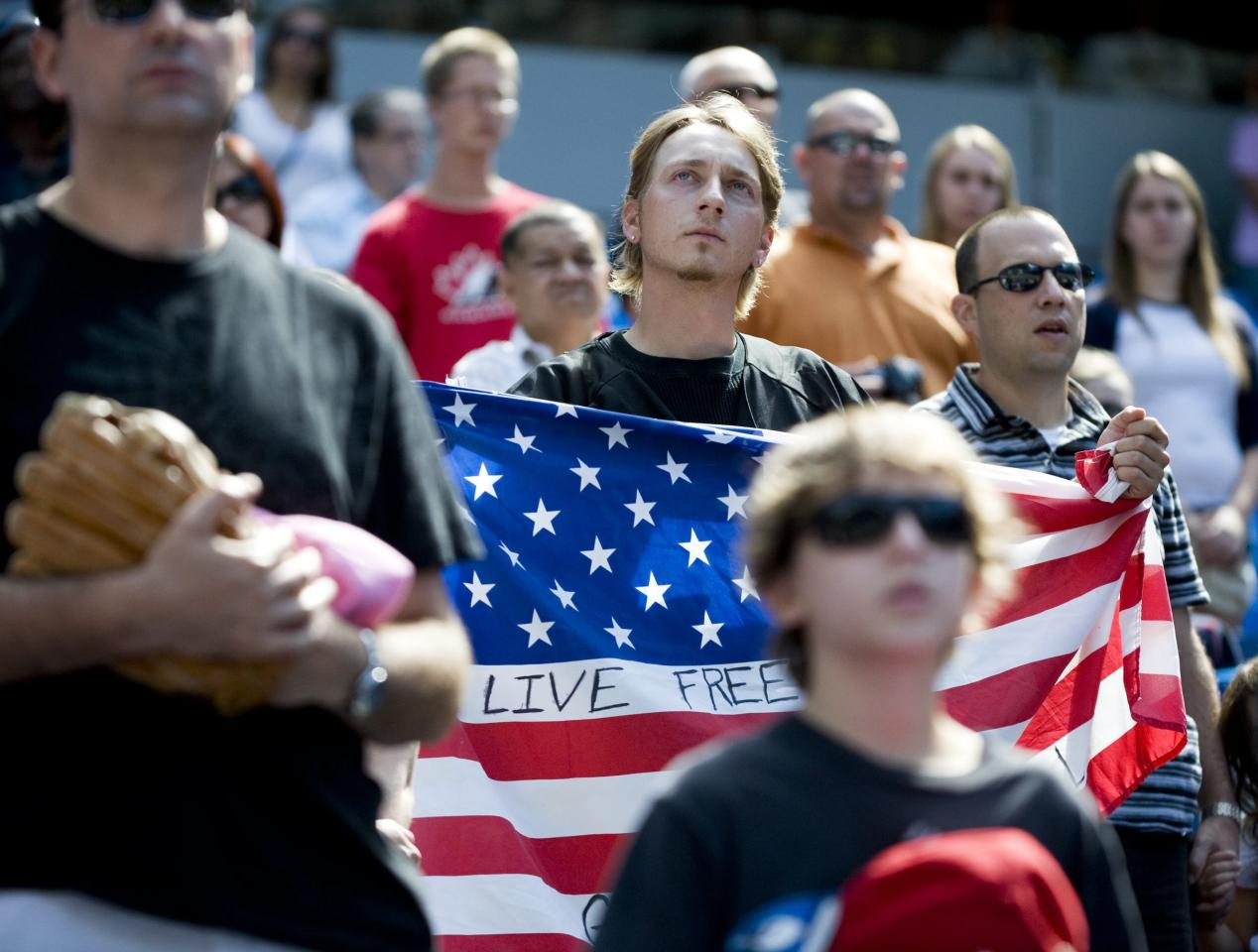 A man holds an American flag during a moment of silence in honor of the 10th anniversary of Sept. 11, 2001 before a baseball game between the Toronto Blue Jays and Baltimore Orioles, Sunday, Sept. 11, 2011, in Toronto. (AP Photo/The Canadian Press, Aaron Vincent Elkaim)