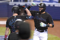 Miami Marlins' Miguel Rojas, right, is met by Corey Dickerson after hitting a solo home run during the first inning of a baseball game against the Milwaukee Brewers, Saturday, May 8, 2021, in Miami. (AP Photo/Lynne Sladky)