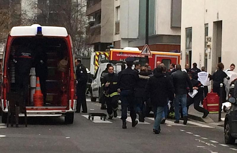 Firefighters and police officers gather in front of the offices of the French satirical newspaper Charlie Hebdo in Paris (AFP Photo/Philippe Dupeyrat)