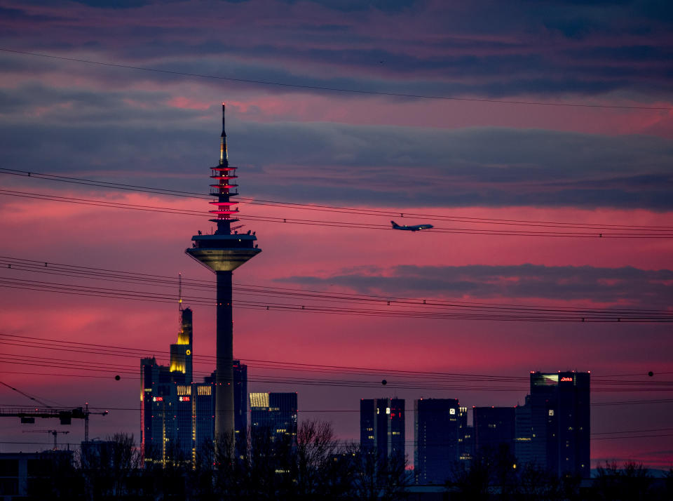 An aircraft passes a television tower and buildings of the banking district as it approaches the airport in Frankfurt, Germany, just before sunrise on Sunday, Feb. 16, 2020. (AP Photo/Michael Probst)