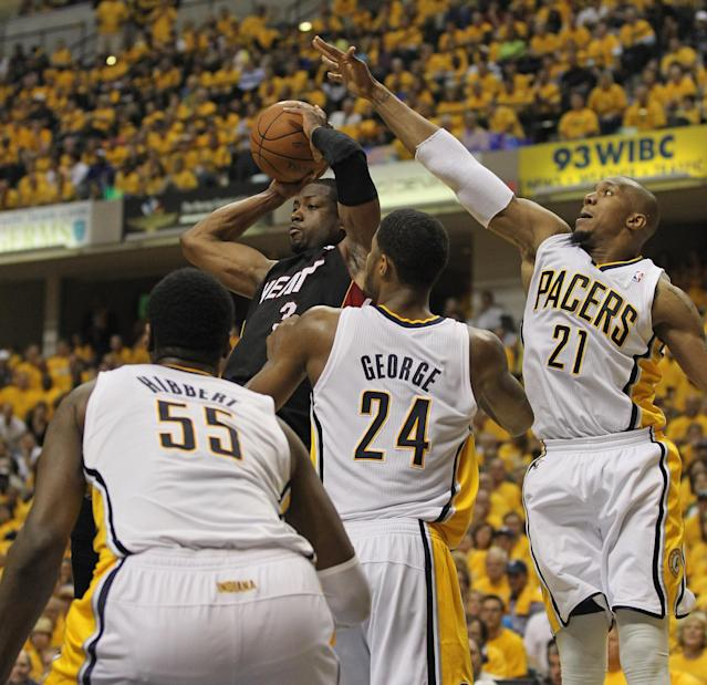 INDIANAPOLIS, IN - MAY 24: Dwyane Wade #3 of the Miami Heat leaps to pass over (L-R) Roy Hibbert #55, Paul George #24 and David West #21 of the Indiana Pacers in Game Six of the Eastern Conference Semifinals in the 2012 NBA Playoffs at Bankers Life Fieldhouse on May 24, 2012 in Indianapolis, Indiana. NOTE TO USER: User expressly acknowledges and agrees that, by downloading and/or using this photograph, User is consenting to the terms and conditions of the Getty Images License Agreement. (Photo by Jonathan Daniel/Getty Images)