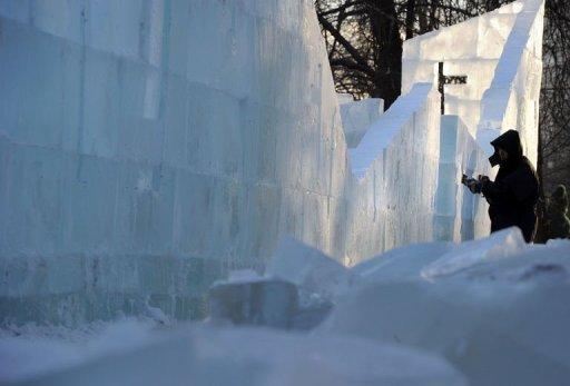 A sculptor works on a wall of the ice fortress in a park in central Moscow on December 23, 2012