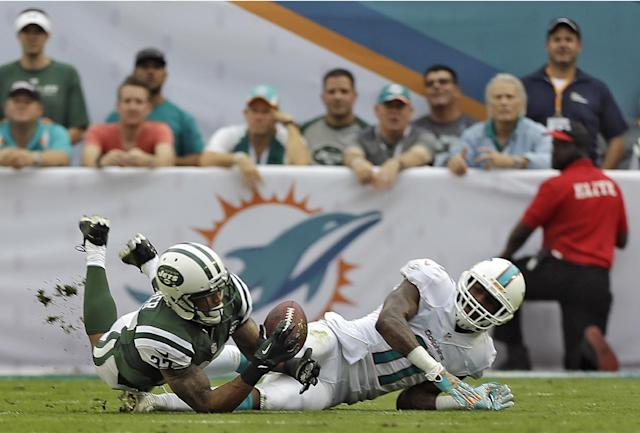 New York Jets cornerback Dee Milliner (27) intercepts a pass intended for Miami Dolphins wide receiver Mike Wallace (11) during the third quarter of an NFL football game Sunday, Dec. 29, 2013, in Miami Gardens, Fla. (AP Photo/Alan Diaz)