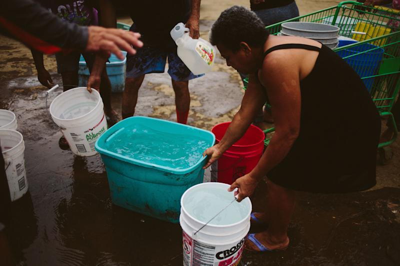 People fill buckets of water in Corozal, Puerto Rico, on Sept. 30. More than half of the island is currently without drinking water. (John Taggart/Bloomberg via Getty Images)