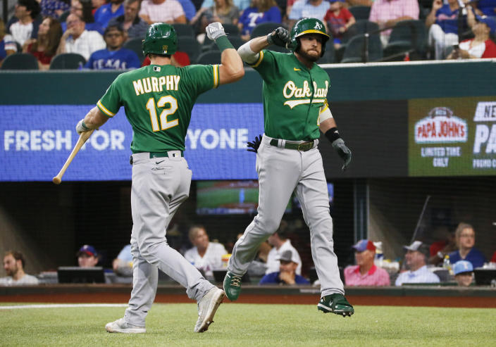 Oakland Athletics' Jed Lowrie, right, is greeted at the plate by Sean Murphy, left, after hitting a solo home run against the Texas Rangers during the second inning of a baseball game in Arlington, Texas, Sunday, July 11, 2021. (AP Photo/Ray Carlin)