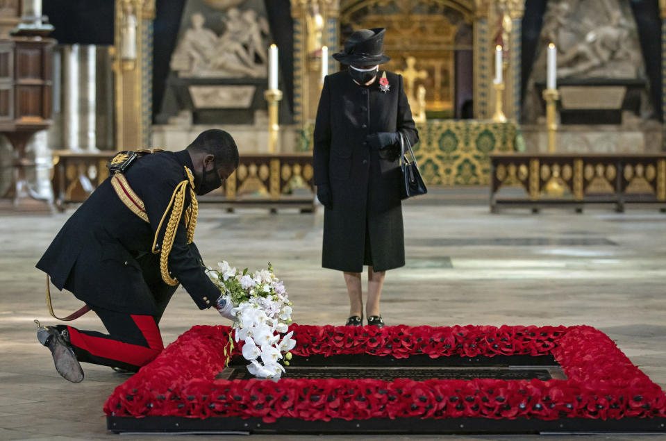 The Queen's Equerry, Lieutenant Colonel Nana Kofi Twumasi-Ankrah, left, places a bouquet of flowers at the grave of the Unknown Warrior on behalf of Queen Elizabeth II, during a ceremony to mark the centenary of the burial of the Unknown Warrior, in Westminster Abbey, London, Wednesday, Nov. 4, 2020. Queen Elizabeth II donned a face mask in public for the first time during the coronavirus pandemic when attending a brief ceremony at Westminster Abbey last week to mark the centenary of the burial of the Unknown Warrior. While the 94-year-old has been seen in public on several occasions over the past few months, she has not worn a face covering. (Aaron Chown/Pool Photo via AP)