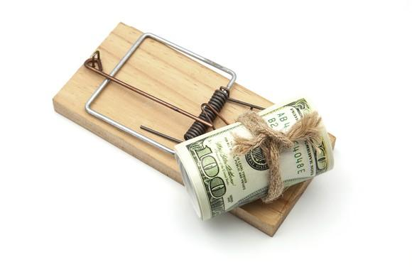 a roll of hundred dollar bills at the end of a mousetrap.