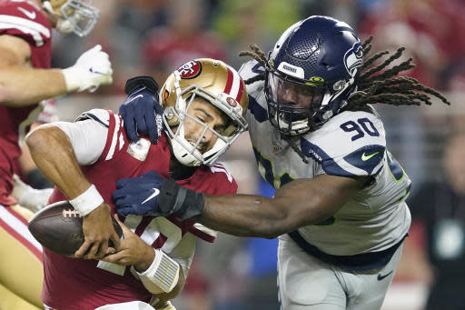 FILE - In this Nov. 11, 2019, file photo, San Francisco 49ers quarterback Jimmy Garoppolo, left, avoids being sacked by Seattle Seahawks defensive end Jadeveon Clowney (90) during the second half of an NFL football game in Santa Clara, Calif. Even with the status of the upcoming season uncertain because of the coronavirus pandemic, teams continue to tinker with their rosters by adding players they hope will help them win whenever, or if, they actually play. Many believed Clowney would be snatched up by a team desperate for a pass-rushing presence during the first few days of free agency. And, for big-time bucks. Instead, the 2014 No. 1 overall pick is still unsigned two months later and potentially looking at a one-year, prove-it deal. A return to Seattle isn't out of the question. (AP Photo/Tony Avelar, File)