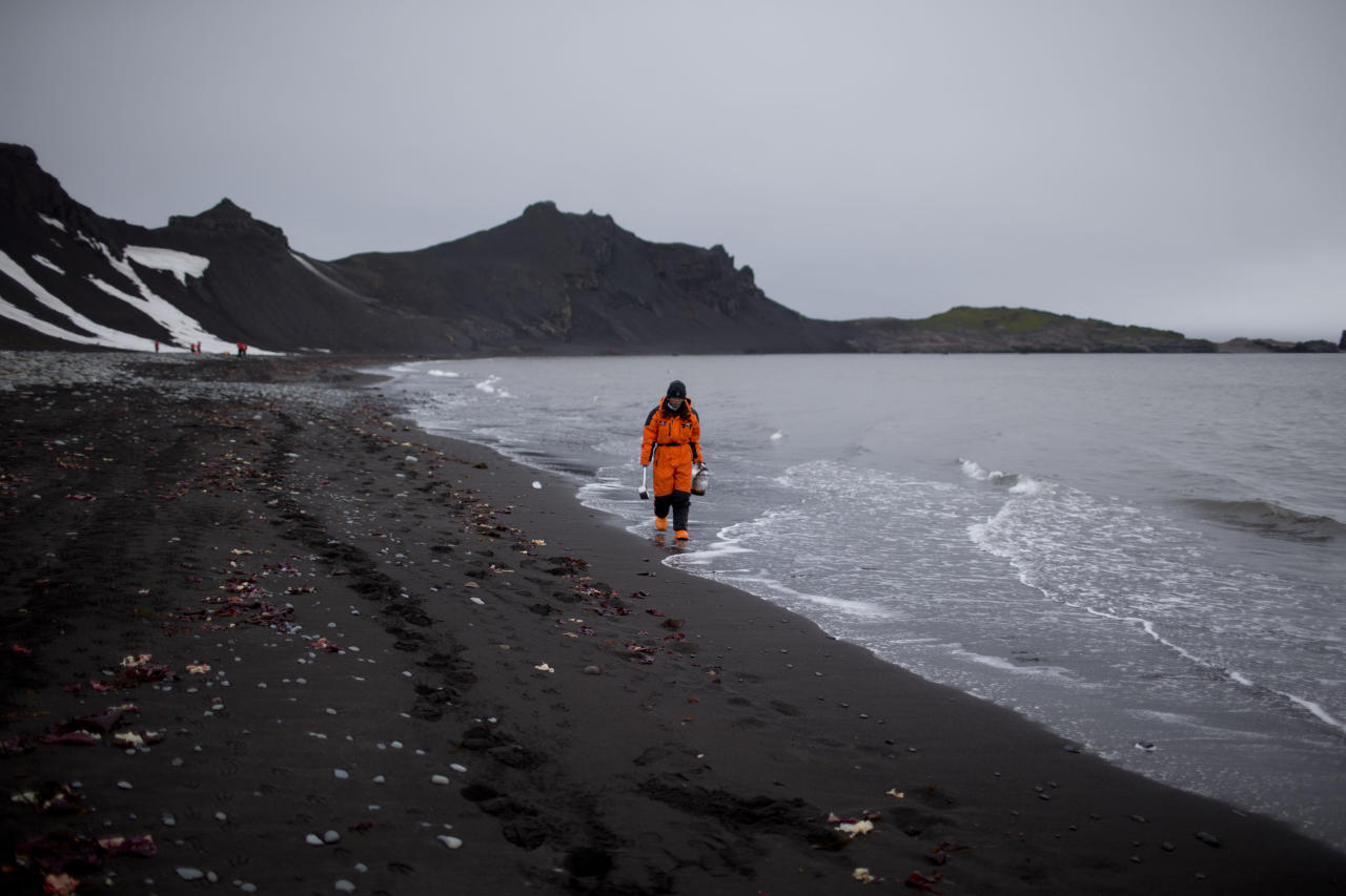FILE - In this Jan. 26, 2015 file photo, Wenjun Li, a marine chemist from China, walks along the beach in search of samples in Punta Hanna, Livingston Island, South Shetland Islands archipelago, Antarctica. Chinese officials plan to detail their ambitions in Antarctica as Beijing hosts a meeting beginning Monday, May 22, 2017 of an international group that oversees management of the polar region. (AP Photo/Natacha Pisarenko, File)