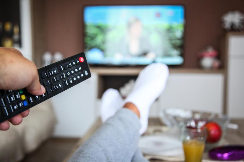 A man holding a remote as he watches TV.