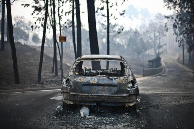 <p>A burned out car is shown on a road after a wildfire in Pedrogao, in central Portugal, June 18, 2017. (Patricia De Melo Moreira/AFP/Getty Images) </p>