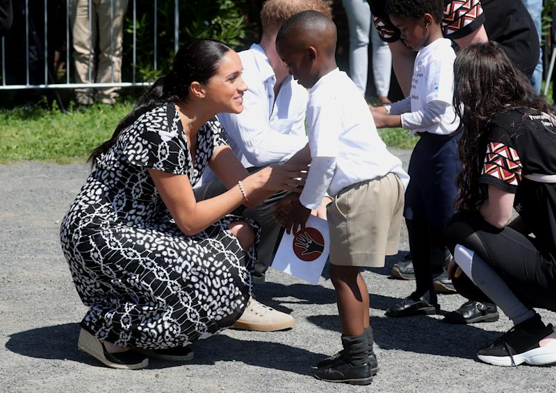 Meghan Markle bends down to talk to a little boy in Africa