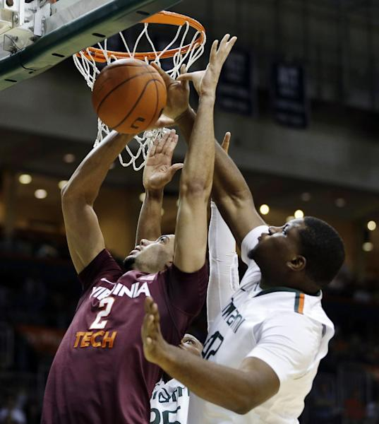 Virginia Tech's Joey van Zegeren (2) shoots between Miami's Kenny Kadji and Reggie Johnson (42) during the first half of an NCAA college basketball game in Coral Gables, Fla., Wednesday, Feb. 27, 2013. (AP Photo/J Pat Carter)