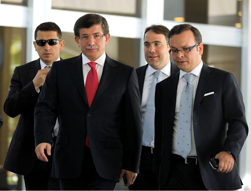 Turkish Foreign Minister Ahmet Davutoglu, centre left, leads advisors as he arrives to speak to the media in Ankara, Turkey, Friday, Sept. 2, 2011. Turkey said Friday it was expelling the Israeli ambassador and cutting military ties with Israel over the last year's deadly raid on a Gaza-bound aid flotilla.  Davutoglu said Turkey was downgrading diplomatic ties to the level of second secretary and that the ambassador and other high-level diplomats would leave the capital Ankara by Wednesday.(AP Photo)