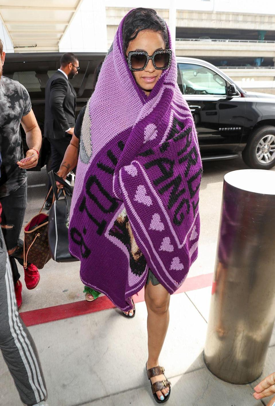 <p><strong>Cardi B, 2018: </strong>The singer showed up to the airport wrapped in a giant purple throw blanket and sported sparkly oversized frames. </p>