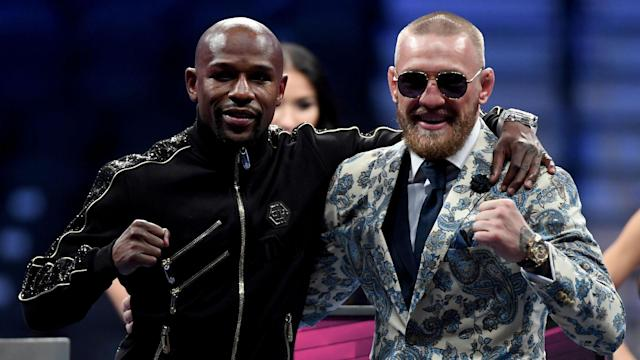 Floyd Mayweather Jr. and Conor McGregor were happy to pose with each other after their big payday. (Getty)