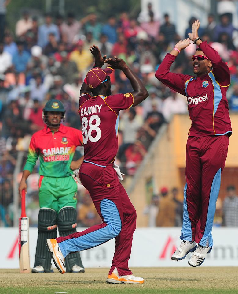 West Indies cricketer Sunil Narine (R) celebrates with his captain Darren Sammy (C) after the dismissal of the unseen Bangladesh cricketer Tamim Iqbal during the first one day international cricket match between Bangladesh and The West Indies at The Sheikh Abu Naser Stadium in Khulna on November 30, 2012. AFP PHOTO/ Munir uz ZAMAN