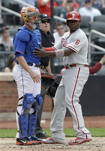 Philadelphia Phillies' Ryan Howard, right, runs into New York Mets catcher John Buck while scoring on a single hit by Chase Utley during the seventh inning of the baseball game at Citi Field, Sunday, April 28, 2013, in New York. (AP Photo/Seth Wenig)