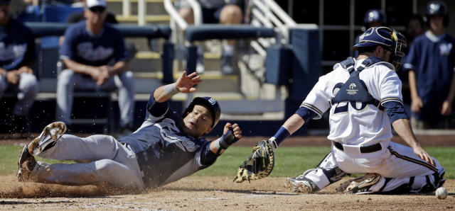 Milwaukee Brewers catcher Jonathan Lucroy can't handle the throw as San Diego Padres' Everth Cabrera scores from first on a single by Alexi Amarista during the second inning an exhibition baseball game Friday, March 7, 2014, in Phoenix. (AP Photo/Morry Gash)