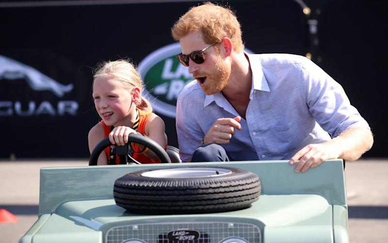 Daimy Gommers, 5, drives the car as Prince Harry rides beside her. - Getty Images North America