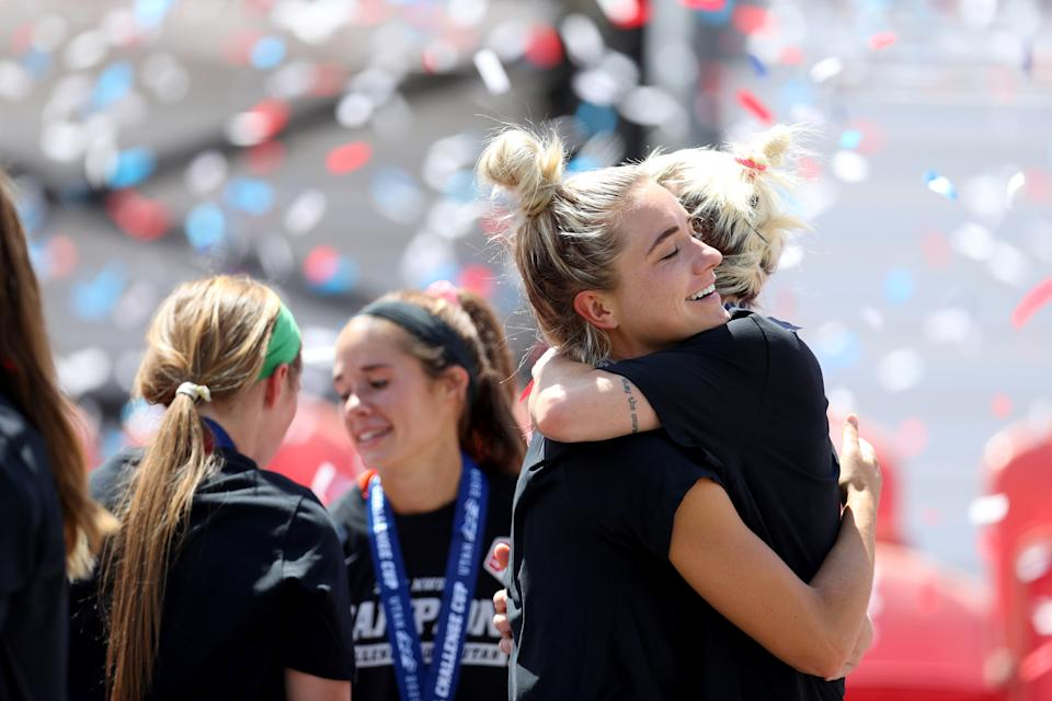 Kristie Mewis and Jane Campbell hug with confetti in the background.