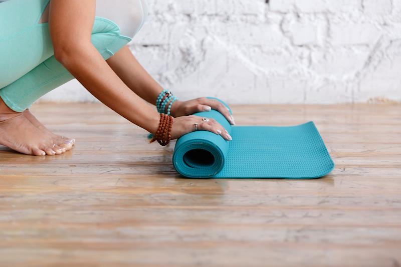 Bare feet and hands of young unidentified woman with bracelets laying out rug for practicing yoga in the gym