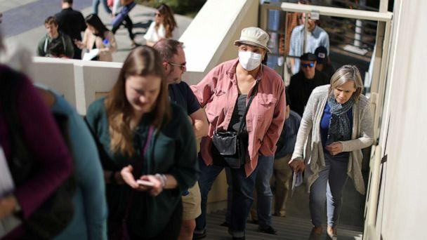 PHOTO: A woman wears a face mask as she lines up to vote at a polling station on Super Tuesday in Santa Monica, Calif., March 3, 2020. (Lucy Nicholson/Reuters)
