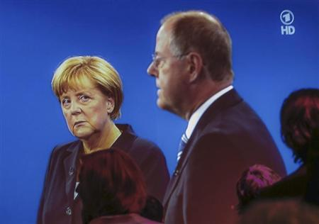People watch a TV duel of German Chancellor Merkel of the CDU with her challenger, the top candidate of the SPD in the upcoming German general elections Steinbrueck, in a culture centre in Berlin